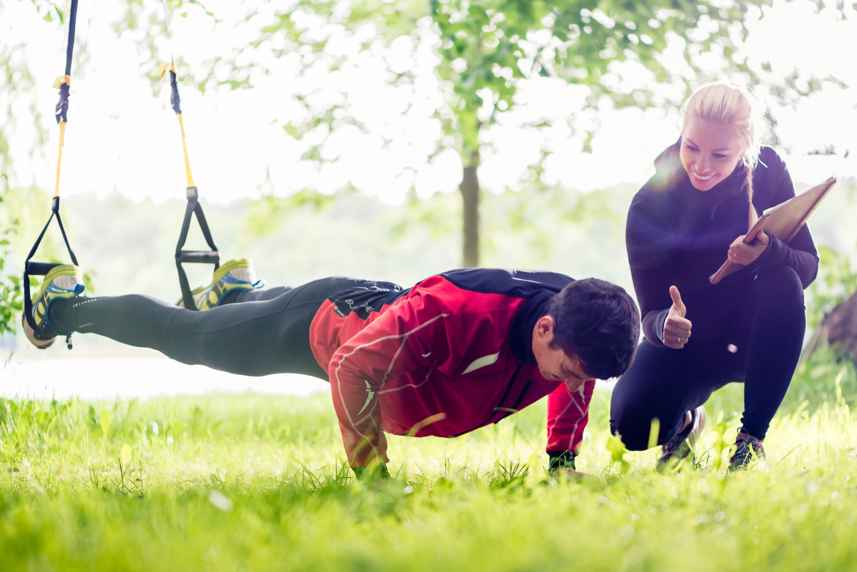 Outdoor Personal Trainer mit Kunde im TRX Schlingentrainer
